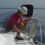 Drifting around Dolphin Bay 3: Gayle scrubbing the deck with a toothbrush.