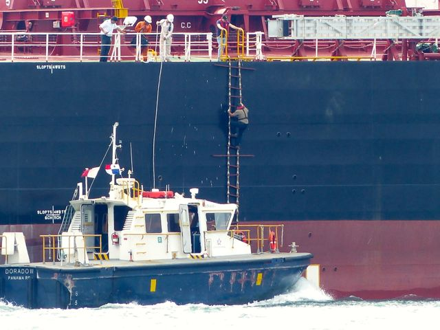 Exiting from a freighter. Both boats are moving at speed: note the bow wave on the small boat.