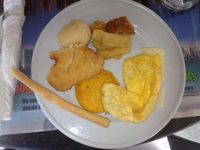 A beige breakfast: coconut breadstick, arepa, hojoldra (fry jack), a bread roll, fried yucca, chicharrón, cheese omelet.